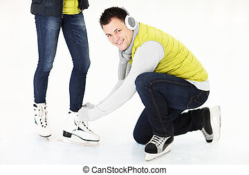 Tying ice skates - A picture of a young man tying his girls...
