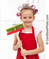 Little housekeeping fairy girl with large hair curls holding...