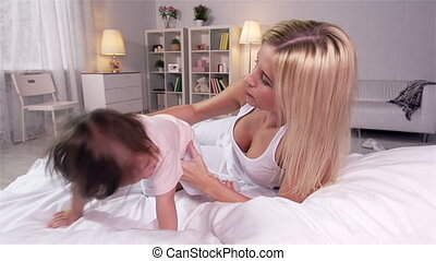 In Bed - Young mother and her toddler daughter cuddling in...