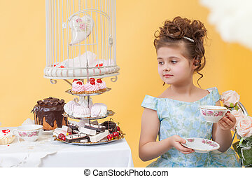 Smartly dressed little lady drinking tea with sweets