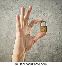 Hand holding padlock with Copyright symbol. Security and...
