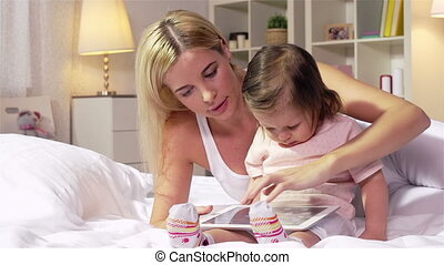 Little Touchpad User - Young mother showing how to use a...