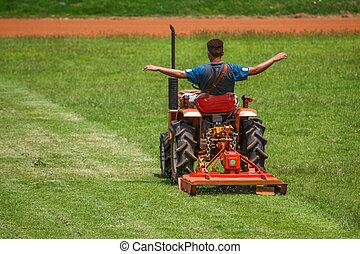 man on mower cutting grass - a man on mower cutting grass in...