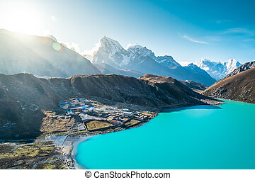 Beautiful snow-capped mountains with lake against the blue...