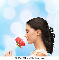 smiling woman smelling flower - nature and beauty concept -...