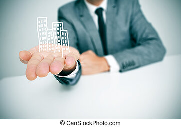 businessman and buildings - a businessman sitting in a desk...