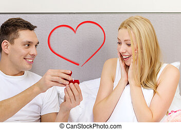 man giving woman little red box and ring in it - hotel,...