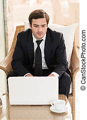 Surfing web in restaurant Confident young businessman using...