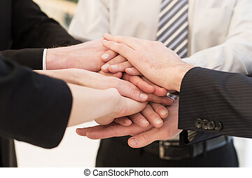 We are team Close-up of many business peoples hands clasped...