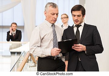 Asking an advice. Two men in formalwear discussing something while moving by staircase with people on background