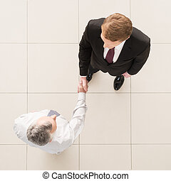 Business partners handshaking Top view of two business men...