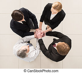 We are team Top view of four people in formalwear standing...