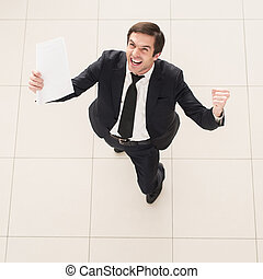The contract is mine! Top view of excited young man in...