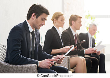 Job candidates Four people in formalwear waiting in line...