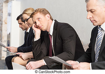 Tired of waiting. Bored young man in formalwear holding head in hand and looking away while sitting in a row with another people