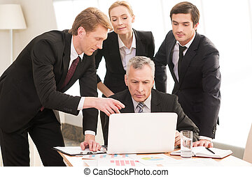 Business discussion. Four business people in formalwear discussing something while one of them pointing laptop
