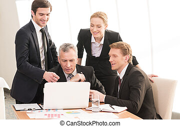 Working on project together. Four smiling business people in formalwear discussing something while one of them pointing laptop