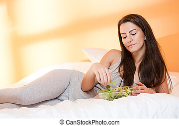 Health food. - Beautiful young brunette woman eating bowl of...