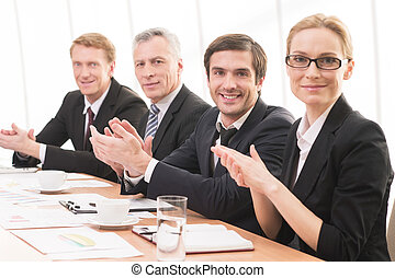 Applauding to you. Four people in formalwear sitting together at the table and applauding you