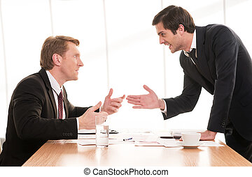 Business conflict. Two young men in formalwear arguing and gesturing while sitting at the table