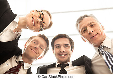 We are strong business team. Low angle view of four cheerful...