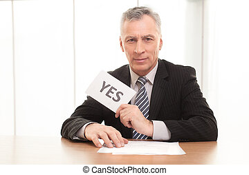 I say yes! Confident senior man in formalwear sitting at the...