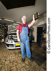 Motor Mechanic - A car mechanic holding up a blank tin with...