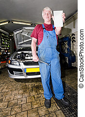 Motor Mechanic - A senior motor mechanic, holding up a blank...
