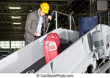 Conveyor belt check point - An airport security worker,...