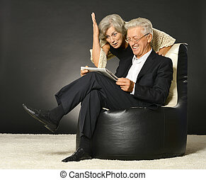Elderly couple reading newspaper - Senior couple reading...
