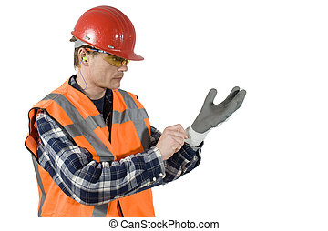 Putting on gloves - A worker, with a hard top, ear plugs and...