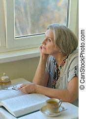 Nice woman is reading book at home