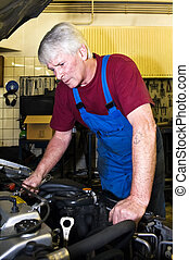 Motor mechanic - A senior motor mechanic servicing a car...