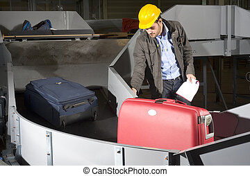 Luggage belt worker - A maintenance engineer inspecting a...