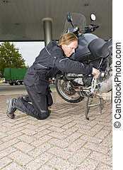 A motorcyclist checking his bike