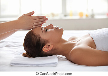 No stress Beautiful young woman lying on back while massage...