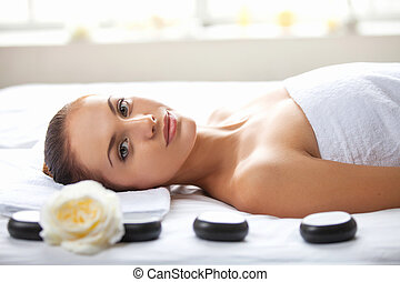 Beauty at spa. Beautiful young woman lying on massage table and looking at camera