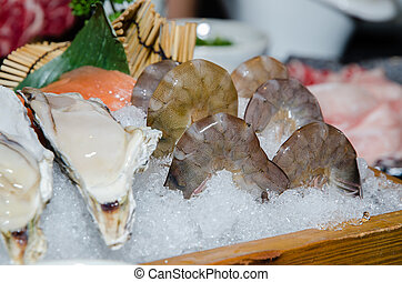 Fresh raw oyster and prawn on ice