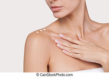 Skin care. Part of beautiful young woman with cream on her shoulder standing against grey background
