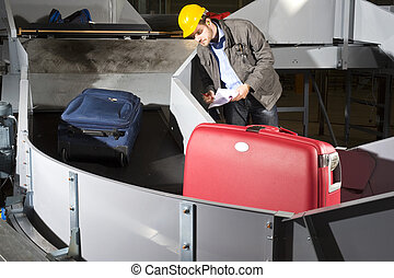 Checking luggage - An airport official checking luggage on a...