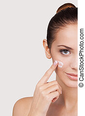 Staying young and beautiful. Cropped image of attractive young woman spreading cream on her face and looking at camera while standing against grey background