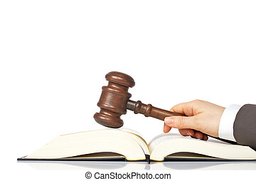 Holding a wooden gavel over the law book - Judge holding a...