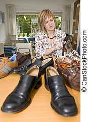 Polishing shoes - A woman sitting at the table busy...