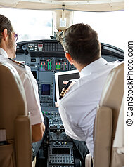 Pilot And Copilot Using Digital Tablet In Cockpit - Rear...