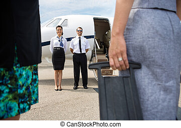 Pilot And Airhostess Standing Near Private Jet - Full length...