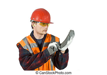 Putting on gloves - A worker, putting on protective gloves...
