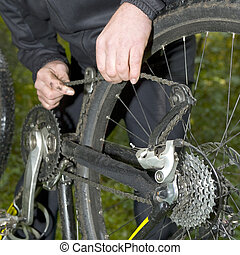Fixing a mountain bike chain during an outdoor practise run
