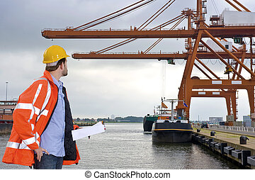 Harbor Inspection - A man wearing a safety coat and a hard...