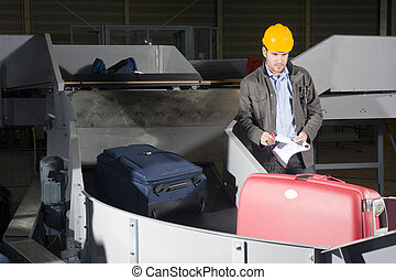 Luggage check at the Airport - A security staff manually...