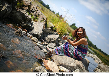 Young girl playing by a river in the summer